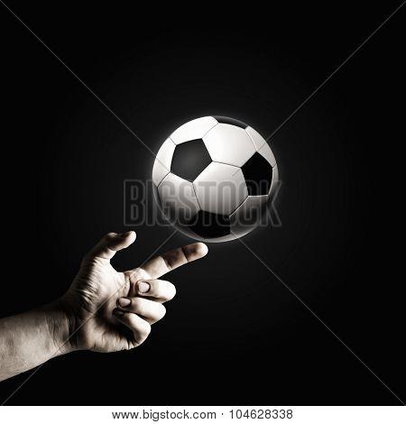 Close up of man hand pointing at soccer ball