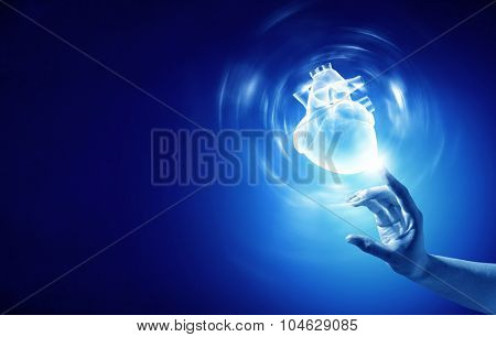 Close up of person hand touching human heart on blue background