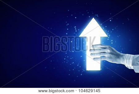 Close up of human hand with arrow icon on blue background