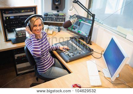 Portrait of happy female radio host at sound mixer desk in studio