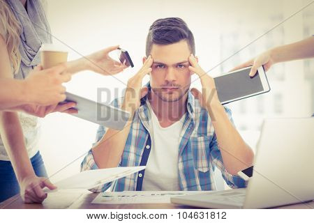 Portrait of depressed businessman with head in hand while sitting at desk
