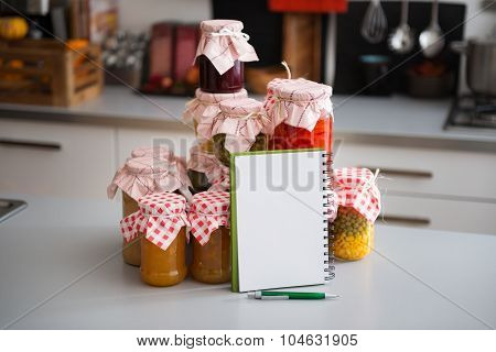 Glass Jars Of Preserved Vegetables With Notebook And Pen