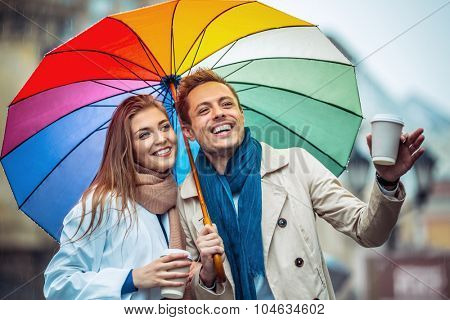 Smiling couple with an umbrella on the street