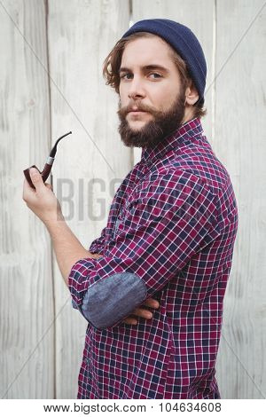 Side view of hipster holding smoking pipe against wooden fence