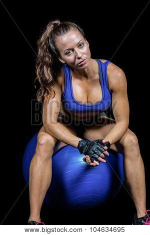 Sporty woman sitting on exercise ball against black background