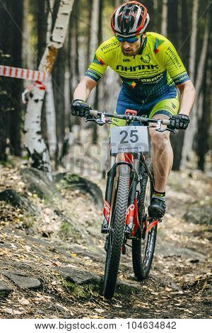 racer cyclist uphill rides over rocks