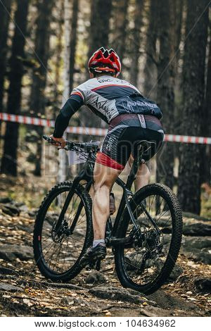 racer cyclist rides along ground and stones