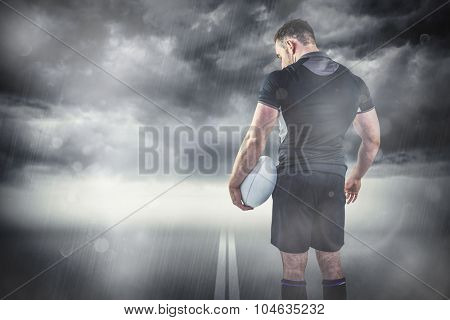 Tough rugby player holding ball against stormy sky
