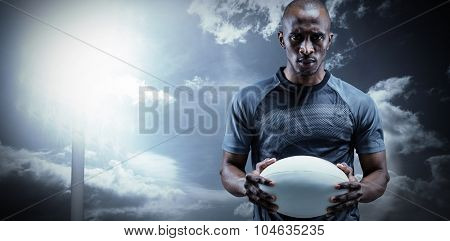 Portrait of serious sportsman holding rugby ball against spotlight in sky
