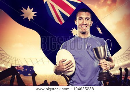Portrait of smiling rugby player holding trophy and ball against large football stadium under cloudy blue sky