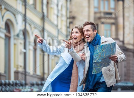 Happy couple with a map outdoors