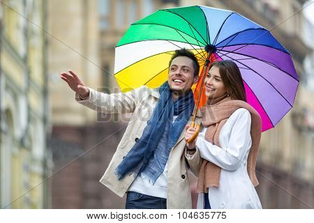 Young couple with an umbrella on the street
