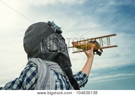 Boy with wooden airplane outdoors