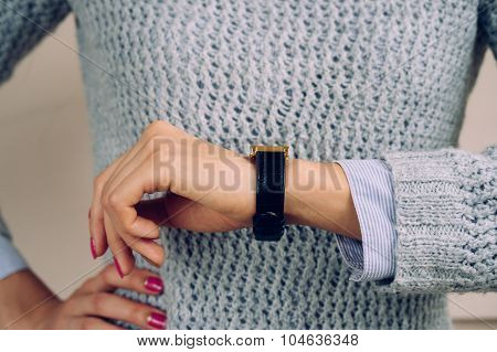 Woman In A Gray Sweater Checks The Time On A Wrist Watch Close-up