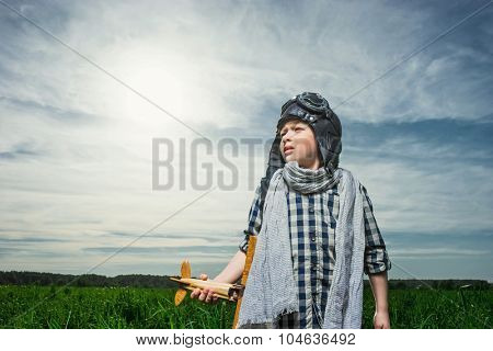 Little boy with wooden airplane outdoors