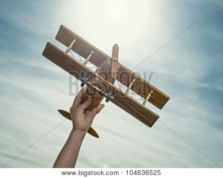 Hand with wooden airplane in the air