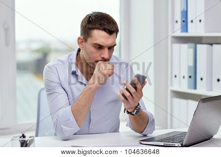 business, deadline, people and technology concept - businessman with smartphone and laptop computer at office