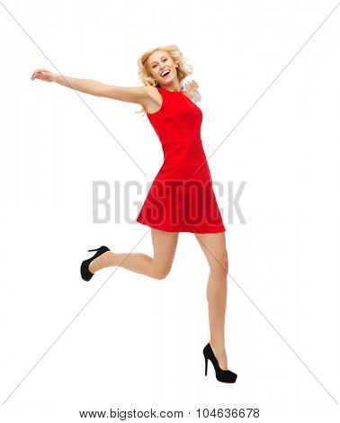 people, emotion, expression, happiness and holidays concept - happy young woman in red dress jumping high in air