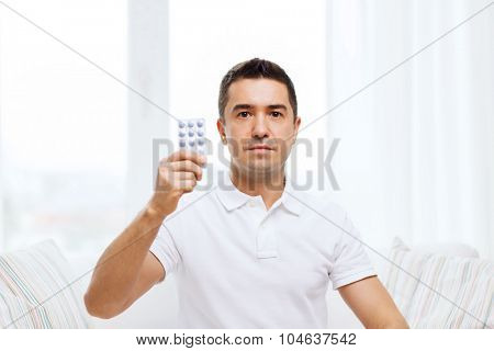 people, medication, medicine and health care concept - man showing pack of pills at home