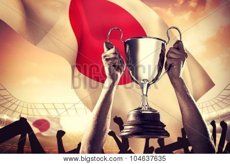 Successful rugby player holding trophy against large football stadium under cloudy blue sky