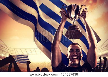 Portrait of successful rugby player holding trophy against large football stadium under cloudy blue sky