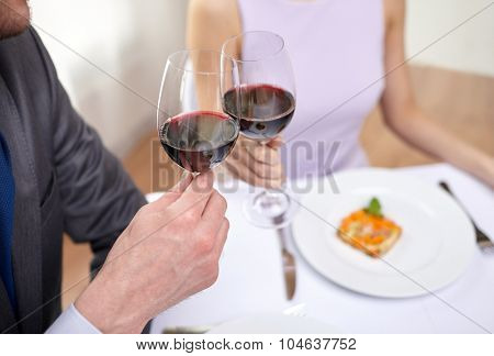 restaurant, people, celebration and holiday concept - close up of young couple with glasses of red wine at restaurant