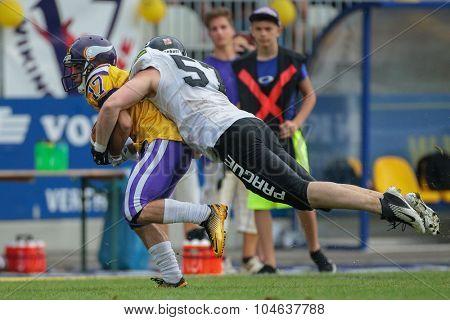 VIENNA, AUSTRIA - JULY 13, 2014: LB Stanislav Kolarik (#57 Panthers) tackles WR Philipp Dubravec (#17 Vikings) during an Austrian football league game.