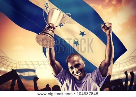Portrait of happy sportsman cheering while holding trophy against large football stadium under cloudy blue sky