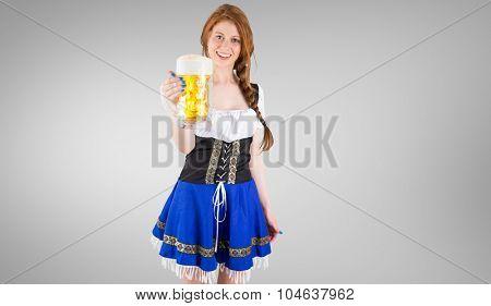 Oktoberfest girl smiling at camera holding beer against grey vignette