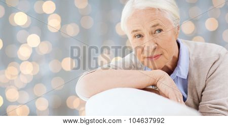 age and people concept - happy smiling senior woman face over holidays lights background