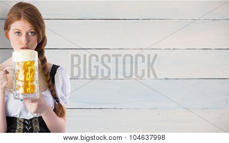 Oktoberfest girl drinking jug of beer against painted blue wooden planks