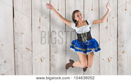 Pretty oktoberfest girl smiling and jumping against wooden background