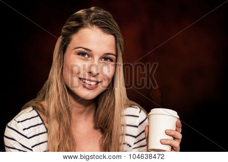 Portrait of smiling female student holding disposable coffee cup against dark background