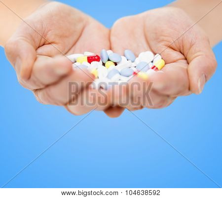 age, medicine, health care and people concept - close up of senior woman cupped hands with pills over blue background