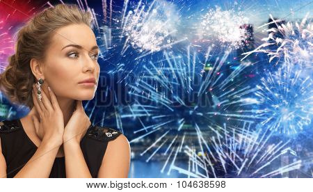 people, holidays and glamour concept - beautiful woman wearing earrings over firework at night city background