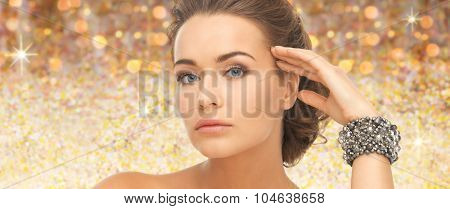 beauty, luxury, people, holidays and jewelry concept - beautiful woman with bracelet over golden lights background
