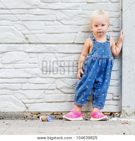 Photo of little child with brick wall on the background