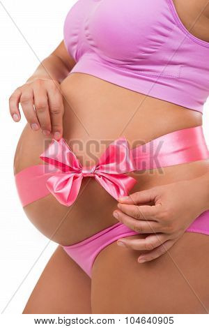 Close Portrait Of A Pregnant Belly With Pink Satin Bow Isolated On White Background. Vertical