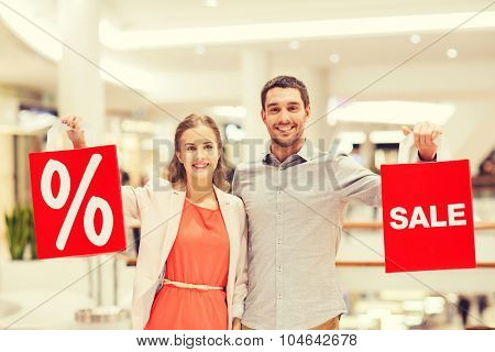 sale, consumerism and people concept - happy young couple with red shopping bags in mall
