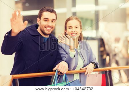sale, consumerism, gesture and people concept - happy young couple with shopping bags waving hands in mall