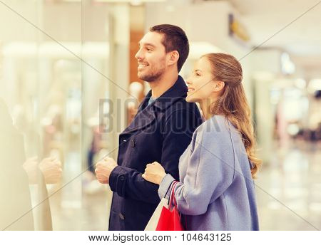 sale, consumerism and people concept - happy young couple with shopping bags looking to shopwindow in mall