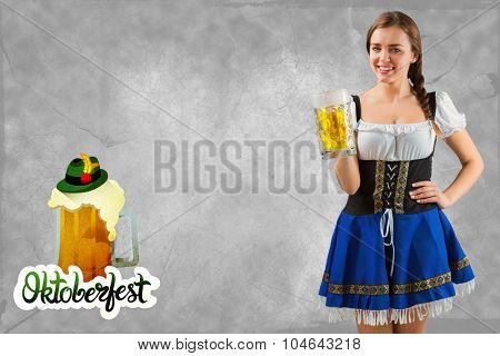 Pretty oktoberfest girl smiling at camera holding beer against oktoberfest graphics