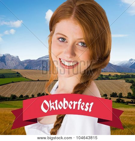 Oktoberfest girl smiling at camera against country scene with mountain