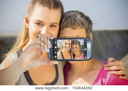 Hand holding smartphone showing against sporty mother and daughter smiling