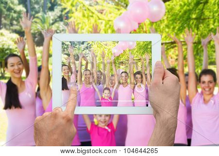 Hand holding tablet pc against smiling women in pink for breast cancer awareness