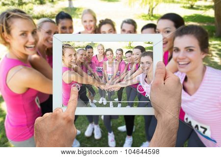 Hand holding tablet pc against smiling women running for breast cancer awareness
