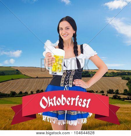 Pretty oktoberfest girl holding beer tankard against country scene