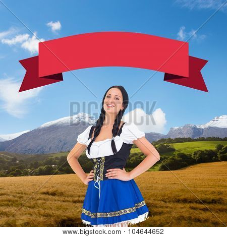 Pretty oktoberfest girl smiling at camera against country scene with mountain