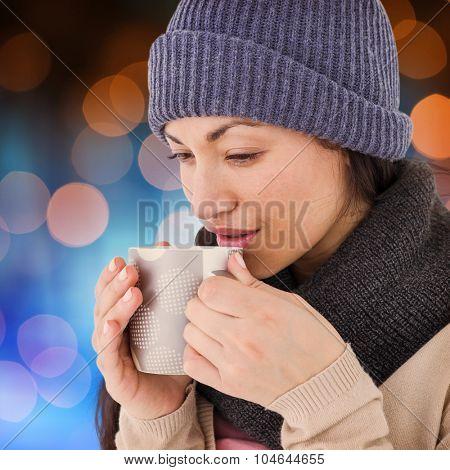 Smiling brunette drinking hot beverage against glowing background