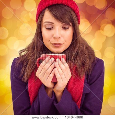 Festive brunette holding a mug against glowing background